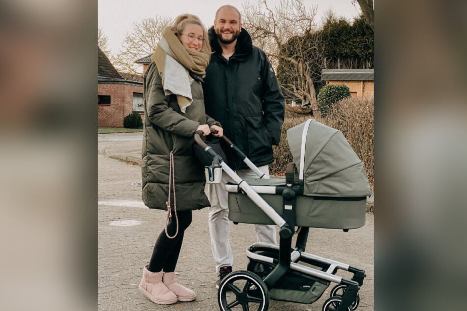 Melissa (29) und Philipp (34) gehen mit ihrem Baby spazieren.