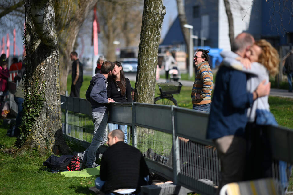 Ein Paar küsst sich an der Deutsch-Schweizer Grenze zwischen Konstanz und Kreuzlingen. Das Paar ist durch einen Grenzzaun getrennt und kann sich nur so umarmen und treffen.