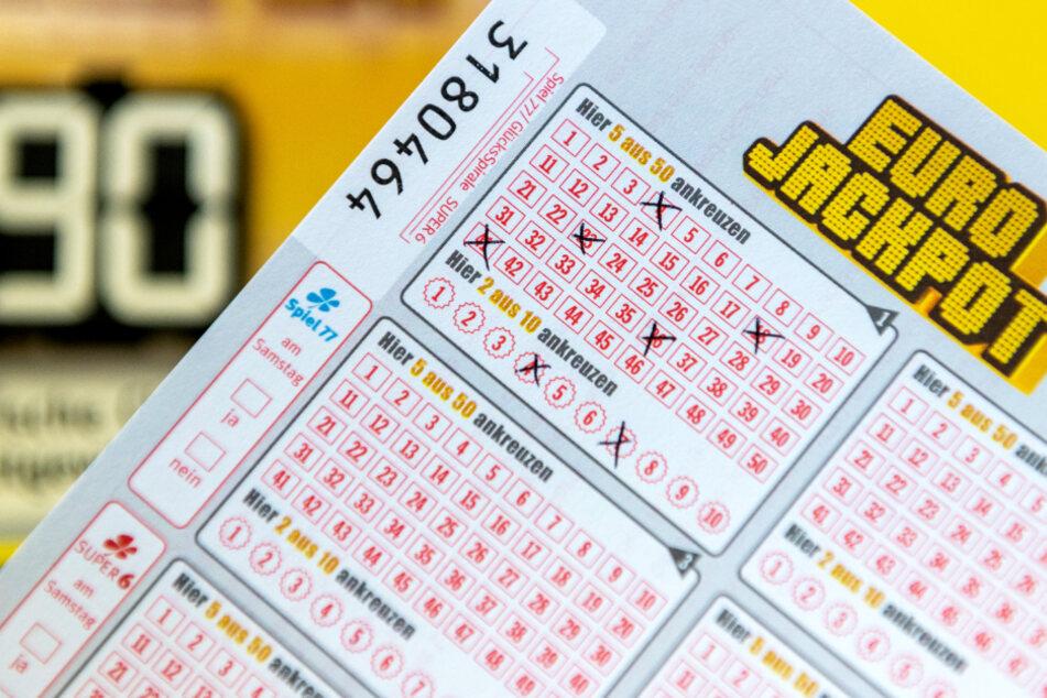 Ein Eurojackpot-Los ist in einer Lotto-Annahmestelle vor einer Tafel zu sehen, auf der auf die Gewinnsumme von 90 Millionen im Eurojackpot hinwiesen wird.