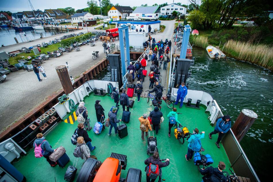 Urlauber mit Fahrrädern und Koffern verlassen im Hafen Vitte auf der Insel Hiddensee das Fährschiff. In Mecklenburg-Vorpommern dürfen nach dem Reiseverbot wegen der Corona-Schutzmaßnahmen nun wieder Urlauber aus anderen Bundesländern zum Urlaub anreisen.