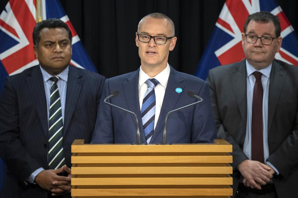 David Clark (M), neuseeländischer Gesundheitsminister und seine Kabinettskollegen Grant Robertson (r), und Kris Faafoi sprechen auf einer Pressekonferenz, auf der Clark seinen Rücktritt bekannt gibt.