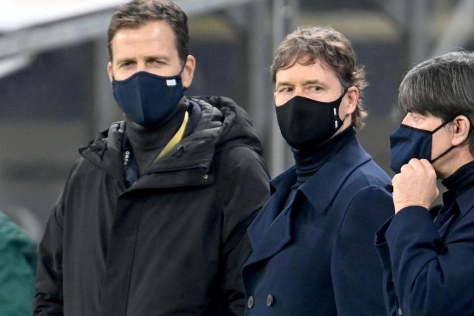 Oliver Bierhoff (l.-r.), Direktor Nationalmannschaften und Akademie, Assistenztrainer Marcus Sorg und Joachim Löw, Trainer von Deutschland, allesamt mit Maske am Spielfeldrand.