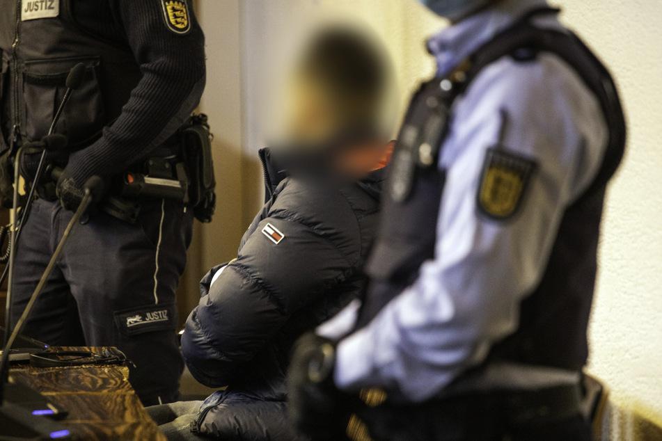 Einer der Angeklagten (Mitte) in dem Vergewaltigungsfall sitzt in einem Saal des Landgerichts Freiburg. Das Urteil gegen ihn gilt nun.