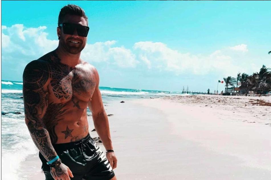 Till Adam (32) posiert am Strand.