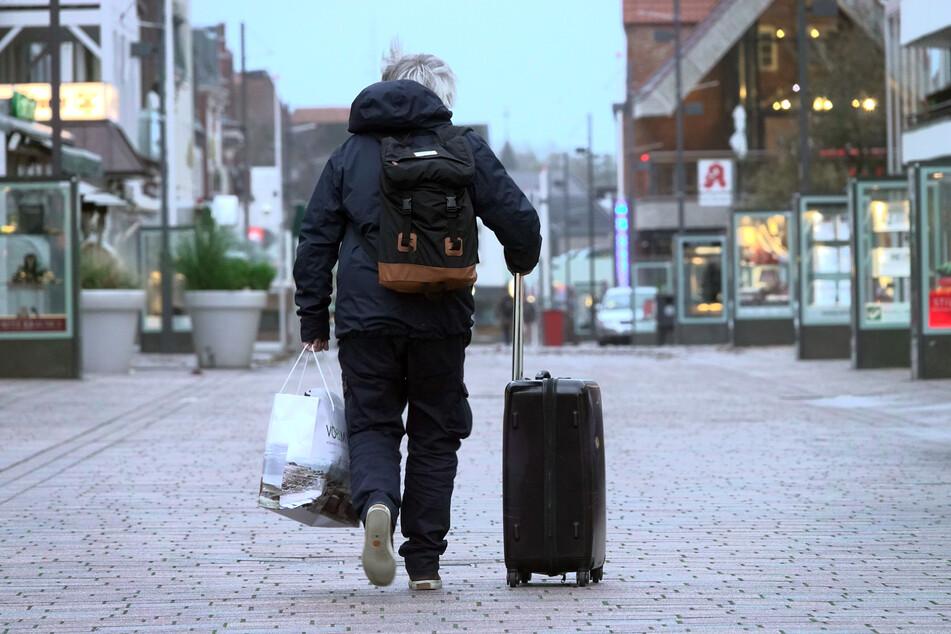 Ein Besucher geht Sylt mit einem Rollkoffer durch eine Füßgängerzone.