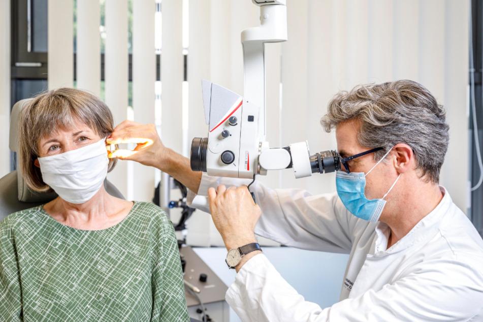 Routineuntersuchung ein- bis zweimal im Jahr: Prof. Marcus Neudert (46) schaut seiner Patientin Angela Knölker (62) mit einem Ohrmikroskop ins Ohr.