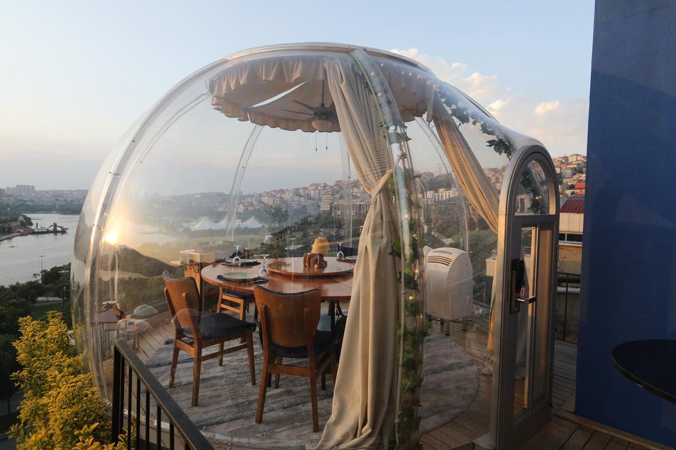 Tische in einem Außenbereich eines Restaurants sind als Maßnahme gegen die Ansteckung der Gäste mit dem Coronavirus mit durchsichtigem Plexiglas in Form von Kuppeln überspannt.