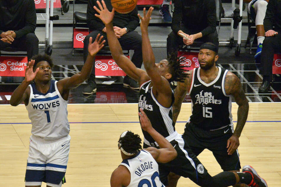 Los Angeles Clippers guard Terance Mann reaches for the rebound over Minnesota Timberwolves forwards Anthony Edwards and Josh Okogie.