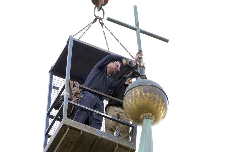 Einsatz in 50 Meter Höhe: Dachdecker Sebastian Keucher sichert das Kruzifix, Metall-Restaurator Thomas Koch (53, l.) flext es ab