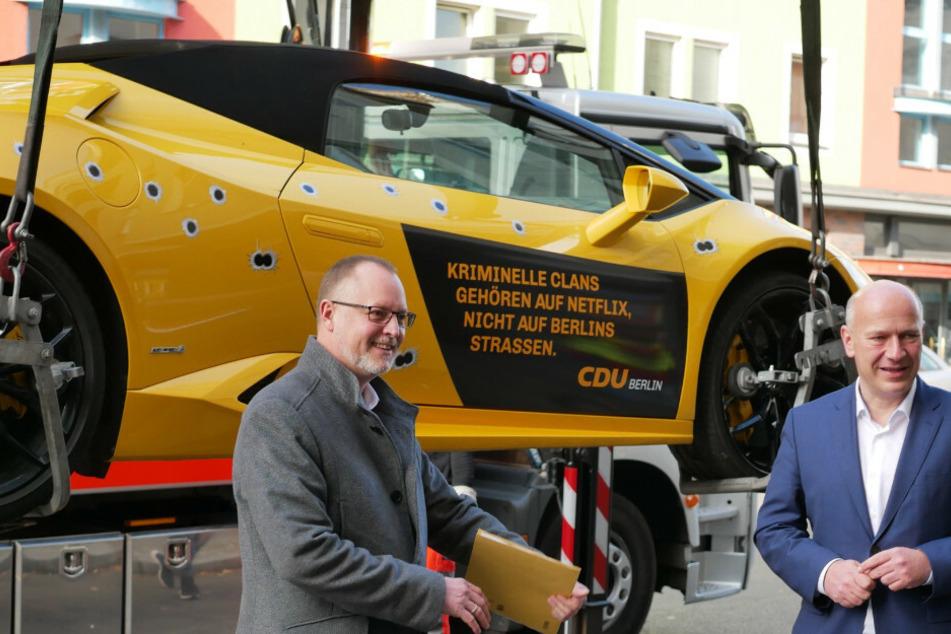 Kai Wegner, CDU-Landeschef (r.), und Falko Liecke (CDU, Neuköllns Gesundheitsstadtrat) stehen vor einem gemieteten Lamborghini mit aufgeklebten Einschusslöchern.