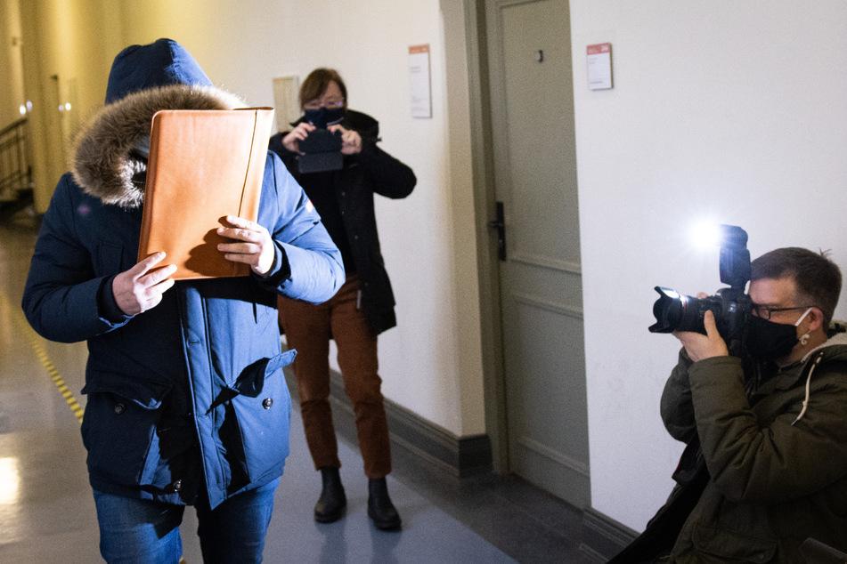 Der Angeklagte geht in den Gerichtssaal im Amtsgericht Altona und verdeckt sein Gesicht vor den wartenden Fotografen mit einer Aktentasche.
