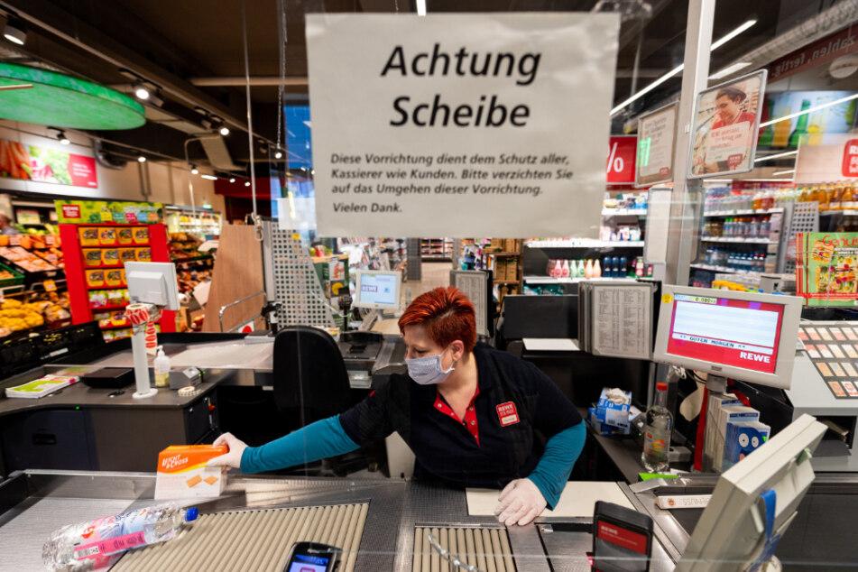 Ein Mitarbeiterin in einem Supermarkt muss trotz Plexiglasscheibe mit Mundschutz arbeiten - das zehrt laut Studie an ihrer Leistungsfähigkeit.