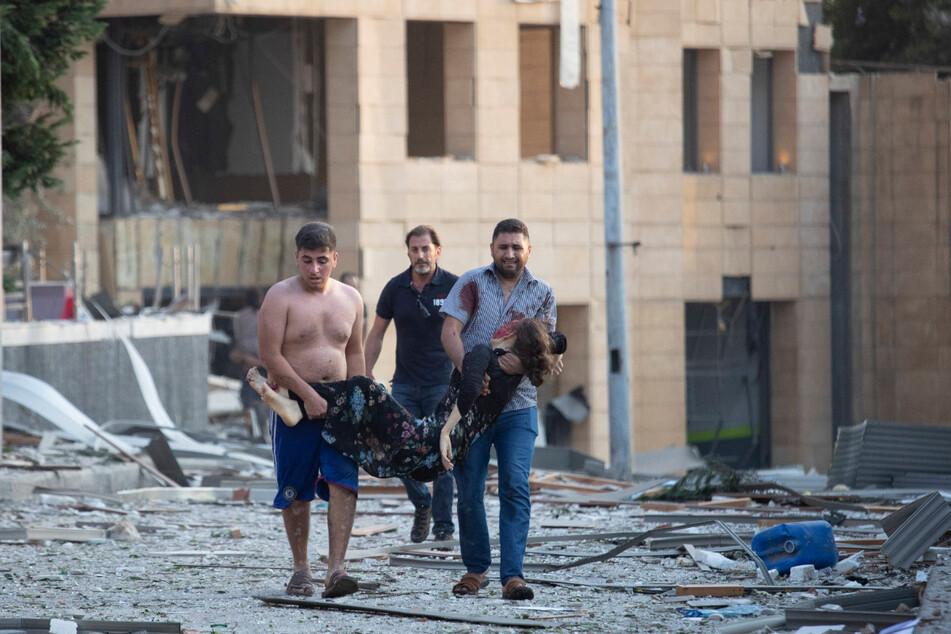 Menschen tragen eine verwundete Frau nach massiven Explosionen in Beirut. Die Explosionen erschütterten die Innenstadt von Beirut und beschädigten Gebäude. Es sollen Hunderte Menschen verletzt worden sein.