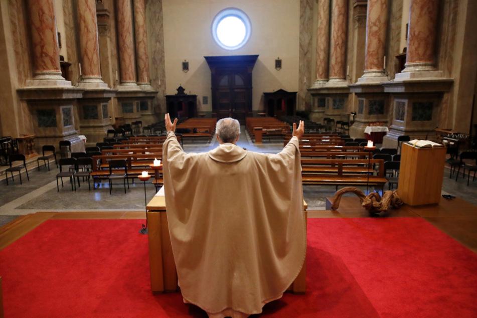 Ein Priester feiert in einer leeren Kirche die Sonntagsmesse.