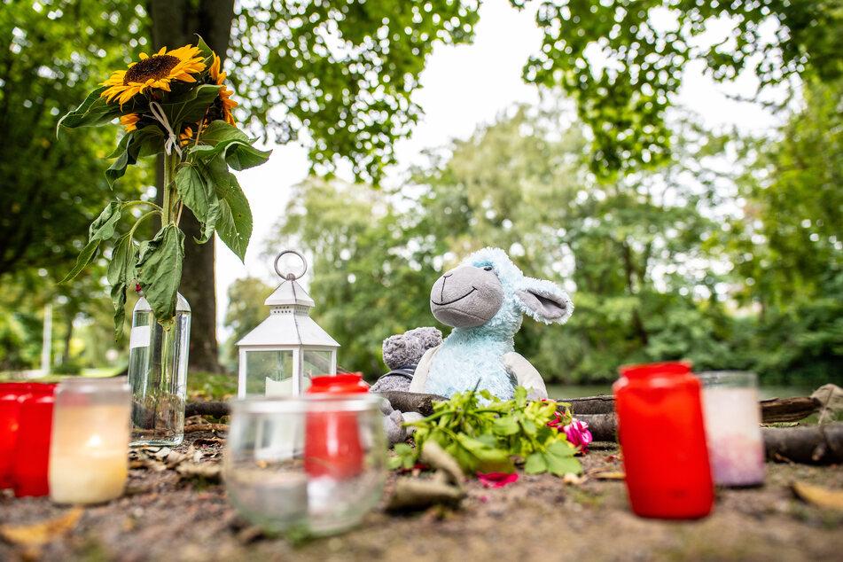 Zwei Stofftiere, Kerzen und Sonnenblumen stehen an dem kleinen See am Oberlandesgericht, wo am Sonntag die Frauenleiche gefunden wurde.