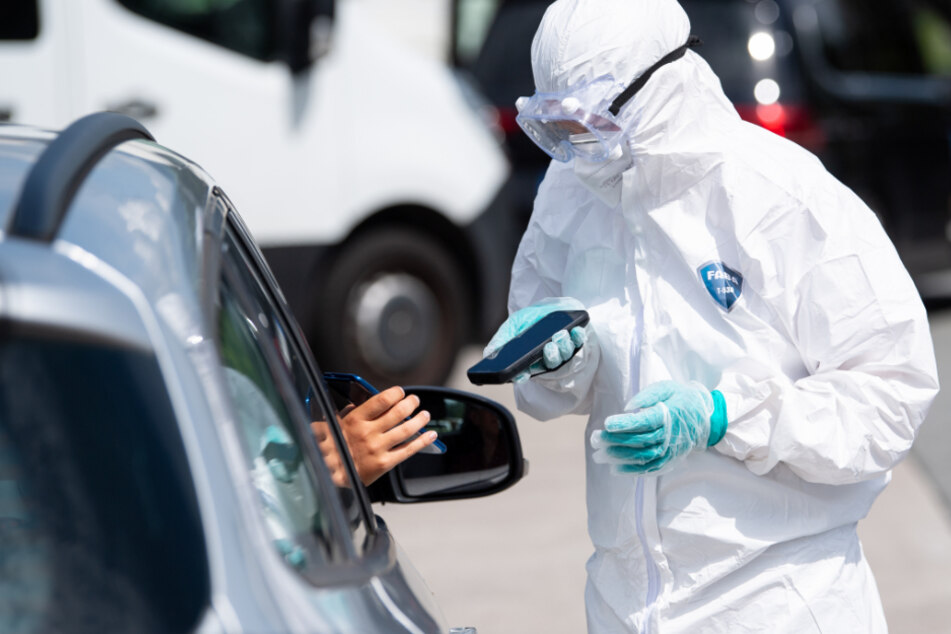 Ein Mitarbeiter der Firma Eurofins scannt an einem Corona-Testzentrum an der Autobahn 93 (A93) an der Rastanlage Inntal-Ost das Smartphone einer Person. (Symbolbild)