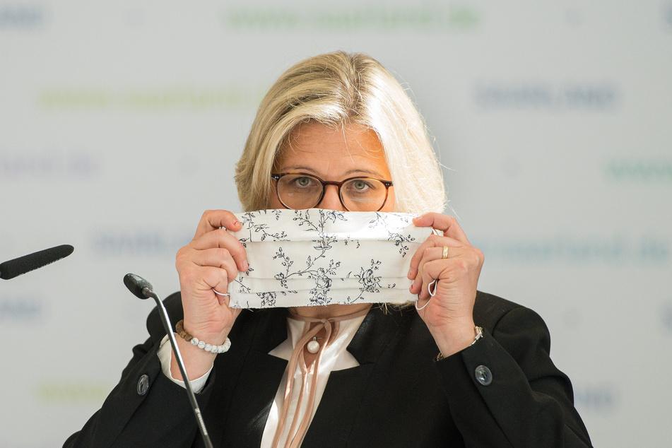 Die saarländische Verkehrsministerin Anke Rehlinger (SPD) legt auf der Pressekonferenz zu den geänderten Maßnahmen zur Eindämmung der Corona-Pandemie zur Verdeutlichung einen Mundschutz an.