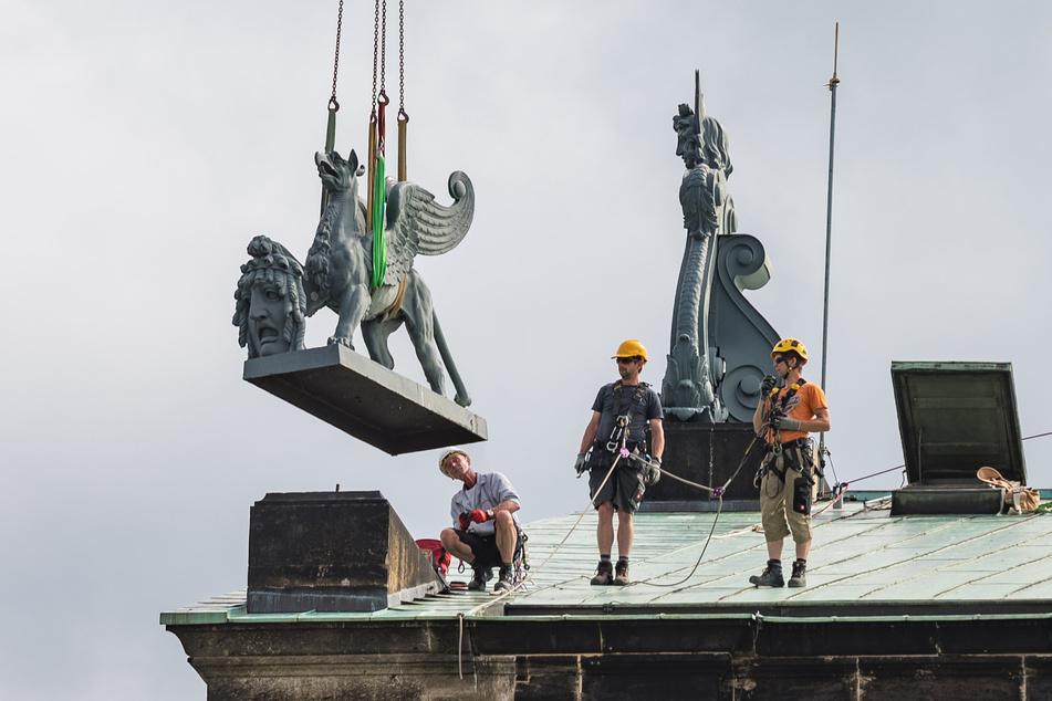 Hier hebt der erste Greif ab. Mit Seilen gesicherte Arbeiter überwachen den Abflug.