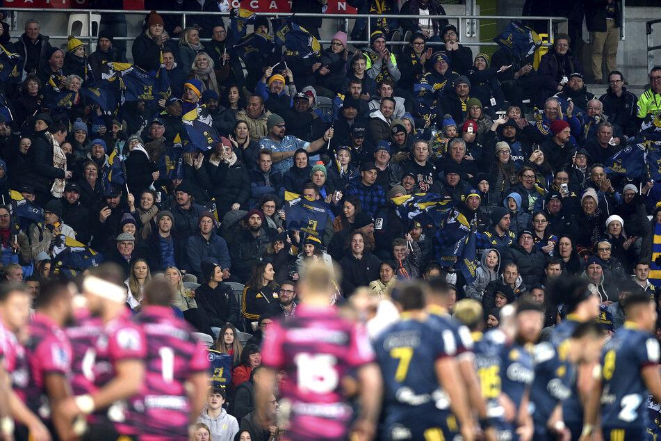 Zuschauer sitzen während eines Rugby-Spiels zwischen den Otago Highlanders und den Waikato Chiefs im Stadion. Über 20.000 Fans haben am 13.06.2020 in Neuseeland das erste Rugby-Spiel seit drei Monaten mit Zuschauern bejubelt.
