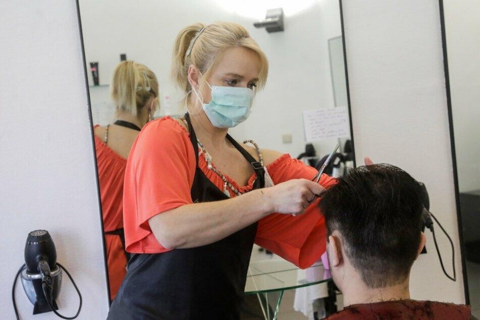 Eine Friseurin mit Mundschutz schneidet einem Kunden die Haare.