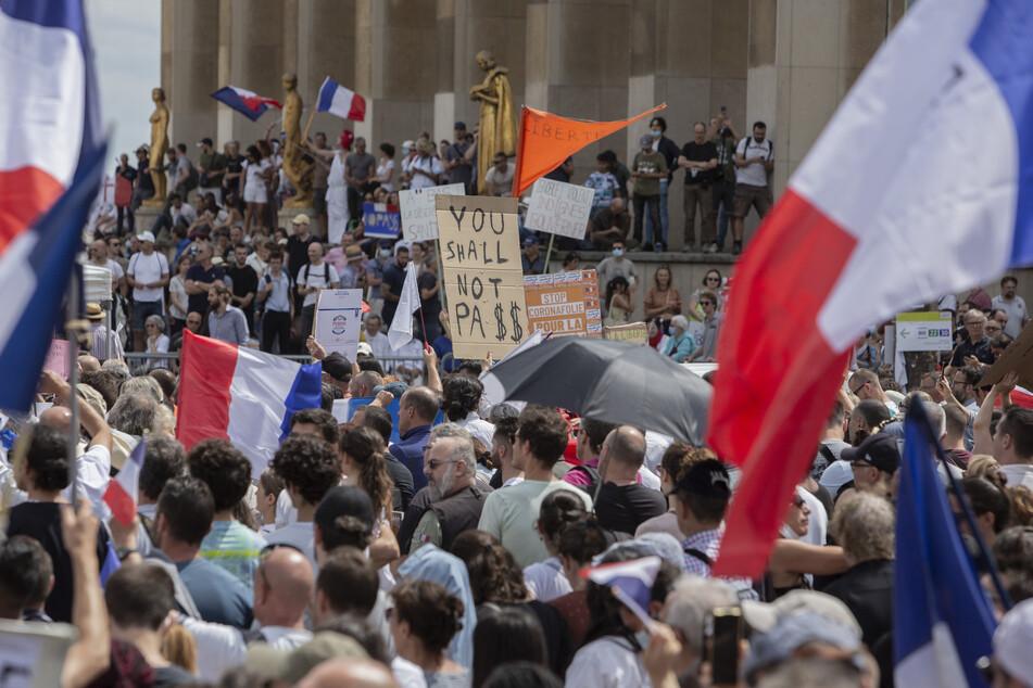 """Demonstranten nehmen auf der """"Droits de l'homme""""-Esplanade am Trocadero-Platz an einem Protest gegen die Impfpflicht für bestimmte Arbeitszweige und den von der Regierung geforderten obligatorischen Impfass teil."""