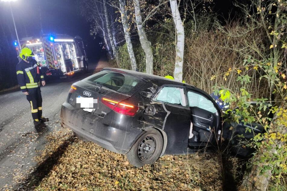 Ein Feuerwehrmann blickt auf den kaputten Audi.