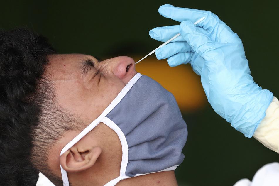 Ein Mediziner macht einem Mann einen Nasenabstrich.