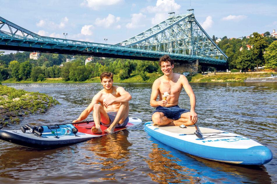 Alex (19,l.) und Felix (20) machten es richig: Die Stand-up-Paddler genossen gestern ihr Eis auf der kühlenden Elbe am Blauen Wunder.