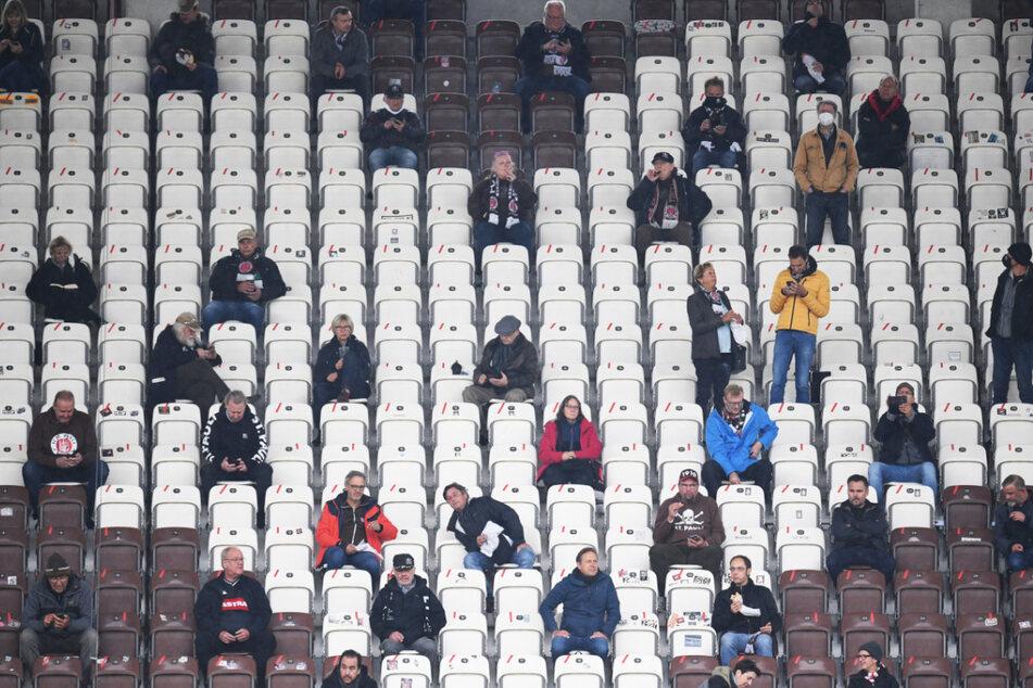 St. Pauli-Fans sitzen vor dem Spiel mit Abstand zueinander auf der Tribüne. (Archivbild)