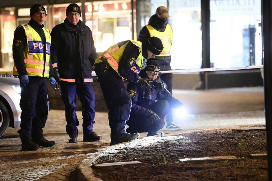 3. März 2021: Polizisten leuchten mit einer Taschenlampe und fotografieren den Boden nach einem Angriff auf mehrere Menschen im südschwedischen Vetlanda.
