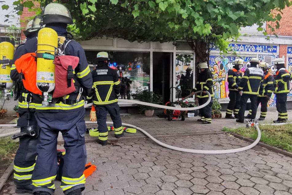 Einsatzkräfte der Feuerwehr stehen am Eingang des Wohnhauses.