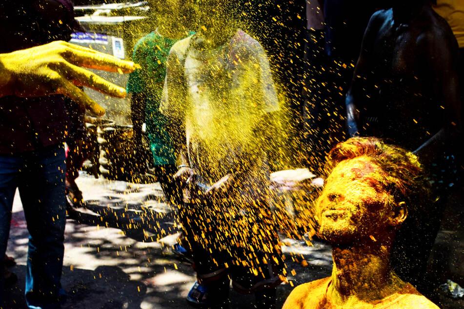 Ein Junge wird während des Holi-Festivals im indischen Kalkutta mit Farbe besprüht.