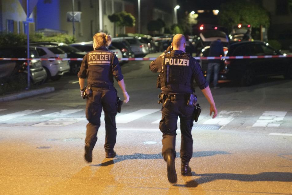 Polizisten gehen am Tattag die Straße in Göppingen entlang.