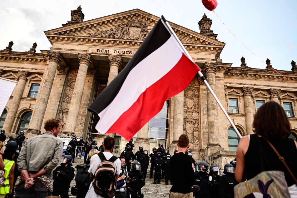Teilnehmer einer Kundgebung gegen die Corona-Maßnahmen stehen Ende August vor dem Reichstag, ein Teilnehmer hält eine Reichsflagge.