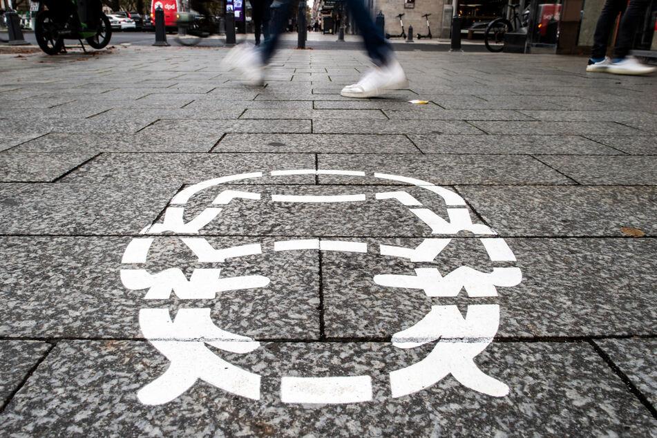 Ein Piktogramm, das auf das Tragen einer Schutzmaske in Düsseldorf hinweist, ist auf den Bürgersteig gemalt.