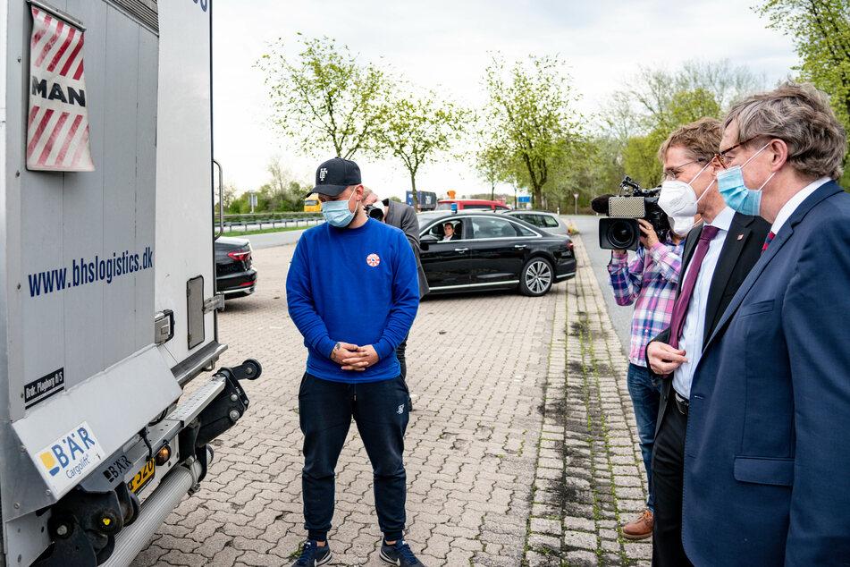 Ministerpräsident Daniel Günther (CDU, 2. v. r.) nimmt das Fahrzeug mit den AstraZeneca-Dosen in Empfang.