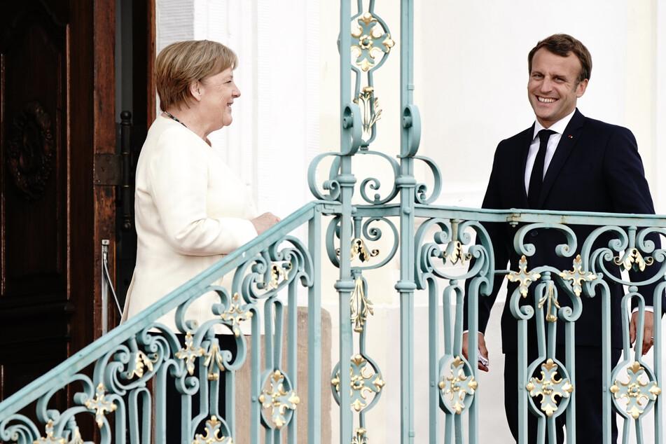 Bundeskanzlerin Angela Merkel (CDU) und Frankreichs Präsidenten Emmanuel Macron begrüßen sich vor Schloss Meseberg, dem Gästehaus der Bundesregierung.