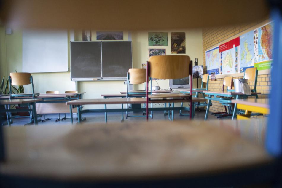 Stühle und Tische stehen in einem Klassenraum mit Abstand nebeneinander. Dabei steht auf jedem Tisch nur ein Stuhl.
