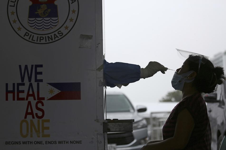 Philippinen, Marikina: Ein medizinischer Mitarbeiter entnimmt an einer Corona-Teststelle eine Abstrichprobe einer Frau für einen Covid-19-Nukleinsäuretest.