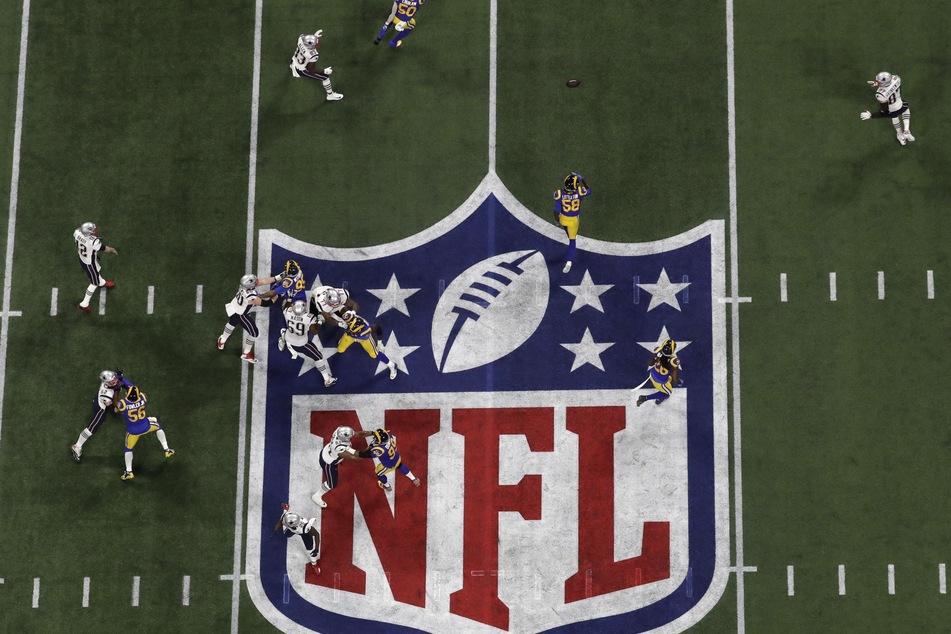 Das Logo der National Football League (NFL) auf einem Rasen, während ein Spiel ausgetragen wird.