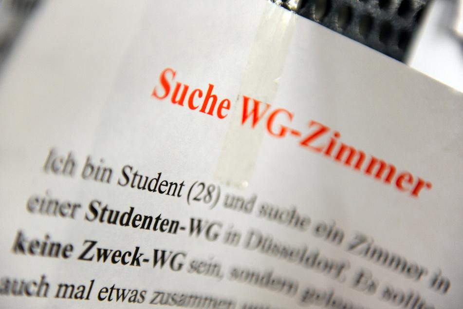 """Ein Zettel mit der Aufschrift """"Suche WG-Zimmer"""" hängt an einem Schwarzen Brett. (Symbolbild)"""