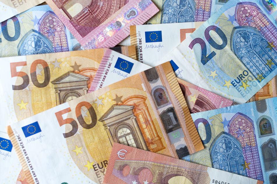 Zahlreiche Banknoten zu 10, 20 und 50 Euro liegen auf einem Tisch.
