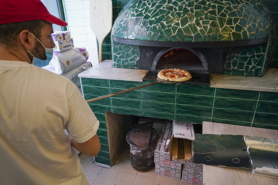 Ein Mann mit Mundschutz nimmt in der Pizzeria Caputo eine Pizza aus dem Ofen.