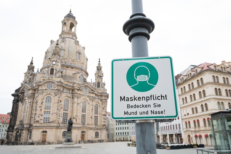 Ein Hinweisschild auf die Maskenpflicht vor der Dresdner Frauenkirche. Diese entfällt nun bei einer Inzidenz unter zehn.