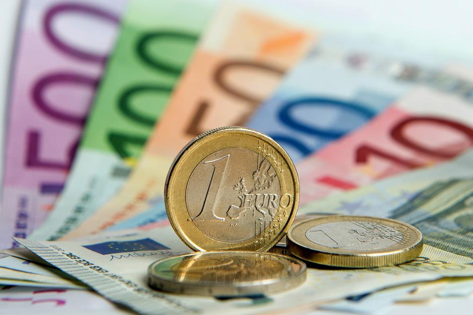 Euro-Banknoten und Euromünzen liegen auf einem Tisch. Gutverdiener sind einer Studie zufolge mit der Krisenpolitik im Schnitt zufriedener als solche mit weniger Einkommen.