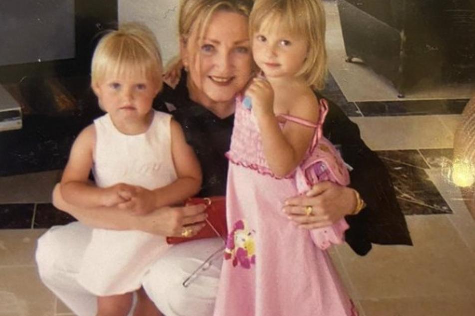 Shania (17, l.) und Davina (18) stehen in den Armen einer blonden Frau, die womöglich die Schwester von Carmen Geiss (56) sein könnte.