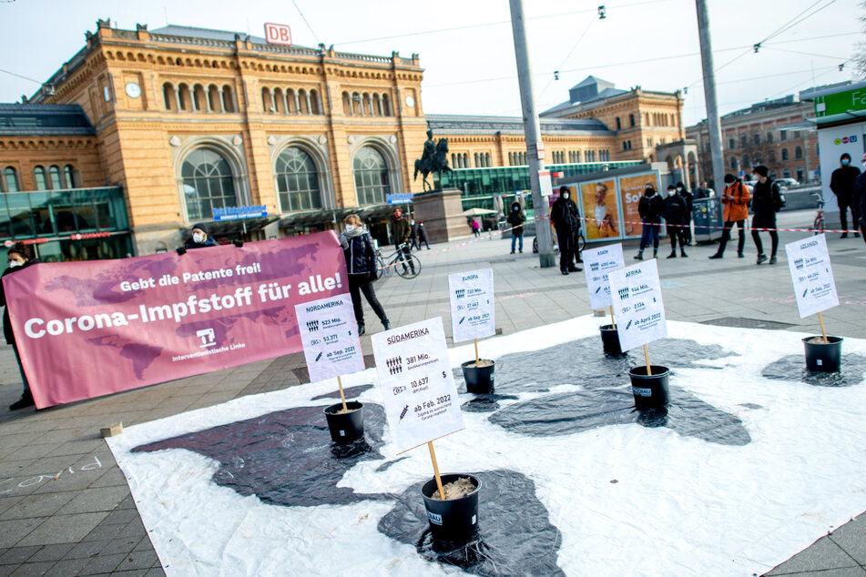 """Hannover: Teilnehmer der Demonstration der Interventionistischen Linken unter dem Motto """"Gebt die Patente frei! Corona-Impfstoff für alle!"""" stehen vor dem Hauptbahnhof."""