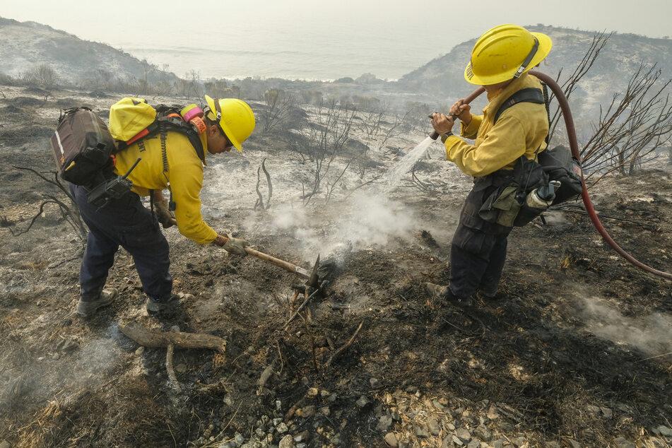 Feuerwehrleute des County of Santa Barbara Fire Departement löschen einen Brand am Straßenrand des Highways 101.