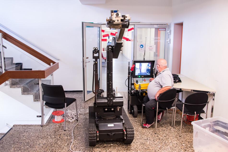 Ein Mitarbeiter navigiert im Amtsgericht Pinneberg einen der Roboter über einen gesperrten Flur.