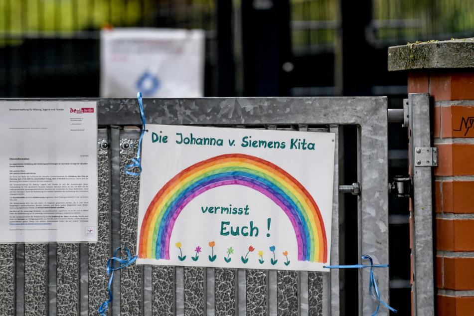 """Berlin: An dem Zaun eines Kindergartens hängt ein Schild mit der Aufschrift """"Die Johanna v. Siemens Kita vermisst Euch!"""""""